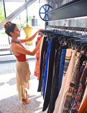 Employee Ashley Liddell staigntens apparel on the racks at The Factory.  mh