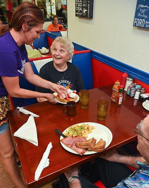 Waitress Renee Wilson serves regulars Virgie and Bob Cherry hearty breakfast dishes, Stawberry Waffle with Whipp Cream and a 8oz Ham with Eggs, Homefries and Wheat Toast, at the All American Diner in Midwest City, 9-18-15. - MARK HANCOCK