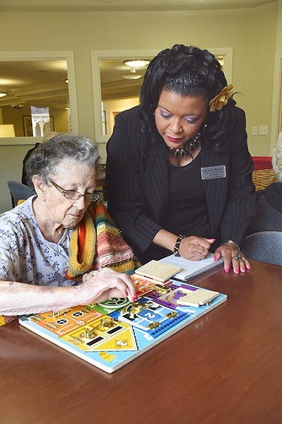 Aquilla Butler, activities coordinator at Prairy Winds Alzheimer's Special Care Center, helps a resident work a puzzle as part of Alzheimer's therapy daily rituals.  mh