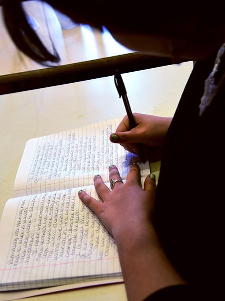 Rhea Brown-Bright, the first named Oklahoma Youth Poet Laureate, works in her notebook recently at the Red Cup coffee shop, located conveniently near Harding Fine Arts Accedemy where she attends high school.  mh