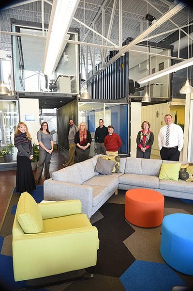 Employees of the Oklahoma Public School Resource Center pose inside with shipping container constructed offices and modern decor.  mh