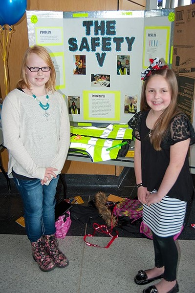 Last year's winners of the Oklahoma Student Inventors Exposition, Kylie Thompson, left, and Jadyn Waddle, both from Heritage Trails Elementary in Moore, are shown with their project. They created a tornado safety vest featuring a colored strobe light, alert whistle, glow sticks, identification holders and other useful implements which could be worn during severe weather. - KEN BEACHLER