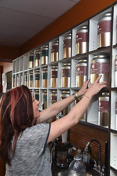 Kristy Jennings, owner of t an Urban Teahouse, selects a tea from a wide variety.  mh