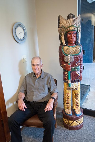 Kent Frates relaxes in the reception area of his office, next to a wooden Indian he collected.  He's quite a collector, with eclectic artifacts displayed around his office.  mh