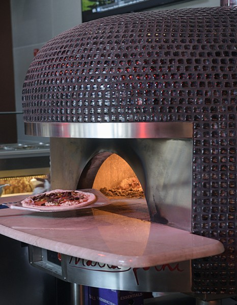 A pizza goes into the custom-built Italian oven at Volare in Norman, Tuesday, Dec. 27, 2016. - GARETT FISBECK