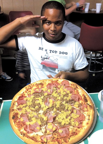 A competitor salutes the camera before attempting the 6-pound Empire Challenge at Papa Angelo's in Bethany. - PROVIDED