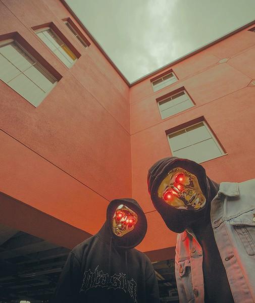 The members of ATLiens keep their identities hidden behind glowing metallic masks. - PROVIDED