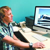 Jeff Bezdek looks at a photo of a Kinkisharyo hybrid streetcar he took at a demo in Dallas. mh