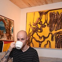 "Moore artist, Maurice Perez, sips on coffee in front of his works, (left to right) ""Calling"" and ""Rule of Three"", 9-24-15."