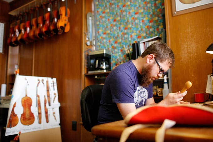 Arsenios Corbishley works on a violin at the Paramount Building in Oklahoma City, Tuesday, Oct. 6, 2015. - GARETT FISBECK