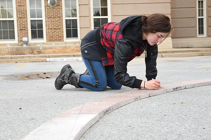 Art student Brittany Standard marks granite pieces for cutting as part of the Coming Together Park sculpture being installed on the USAO campus.  mh