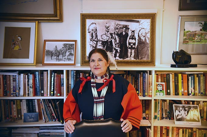 Tracey Satepauhoodle-Mikkanen, executive director of Jacobson House Native Art Center, in the center's cramped office with a historic portrait of the Kiowa Five and Oscar Brousse Jacobson over her shoulder.  The original Kiowa Five included a woman, Lowis Somoky, who steped out and was replaced by James Auchieh.  Officials now refer to the group as the Kiowa Six, puting Smoky back into the group.  2-8-16, at the Jacobson House, 609 Chautauqua Avenue, Norman Oklahoma. - MARK HANCOCK