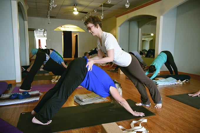 Instuctor Trinity Mays assists a participant during a session at the newly named This Pose Yoga, 7632 N. Western Avenue.  mh
