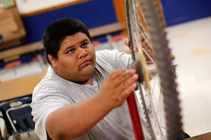 Ruben Cervantes, 16, trues a bicycle wheel at Emerson High School in Oklahoma City, Wednesday, May 6, 2015. - GARETT FISBECK