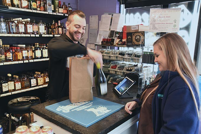 The Wine Gallery owner Adam Duffy checks out customer Brandi Caran, on south Western Avenue in OKC.  mh