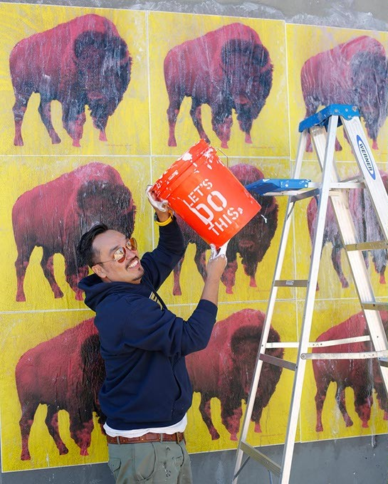 Steven Paul Judd uses wheat paste as he creates a mural on an outside wall of Stash in Norman. - GARETT FISBECK