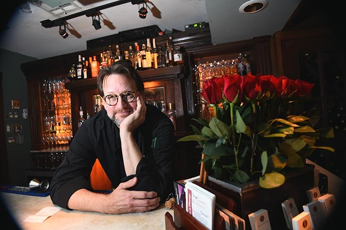 Kurt Fleischfresser takes poses with roses at his position at the reception desk at The Coach House in Nichols Hills, 1-25-16. - MARK HANCOCK