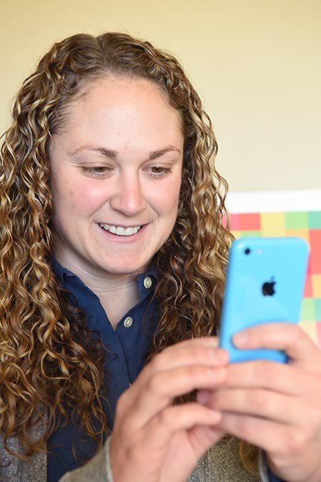 Allison Cofer, the new president of Woven, looks at the new Kickstarter app on a cell phone.  mh