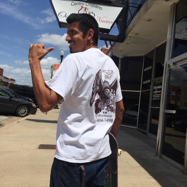 Hector Lopez points to the back of his T-shirt, which features one of his illustrations and his logo.