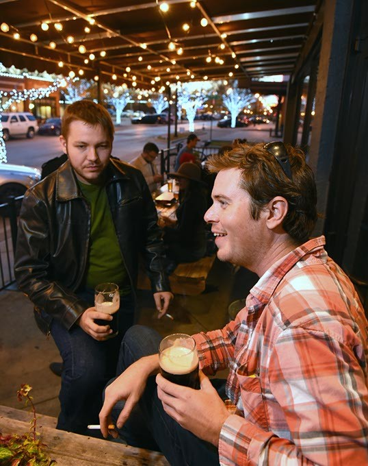 John Lepak and Cody Jennings enjoy Guiness drafts and smokes, on the pateo at Saints in the Plaza District, OKC, 11-25-15. - MARK HANCOCK