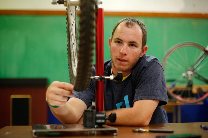 Brendan Heitz, a mentor from the University of Oklahoma, helps true a bicycle wheel at Emerson High School in Oklahoma City, Wednesday, May 6, 2015. - GARETT FISBECK