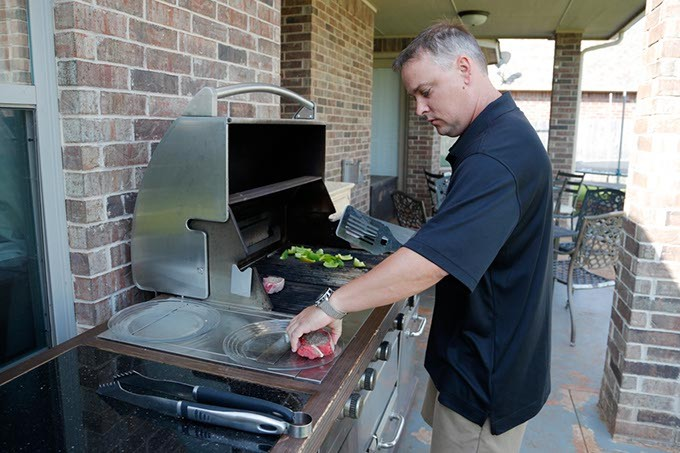 Billy Wilson, owner of Opus Prime Steakhouse, cooks steak at his home. (Garett Fisbeck)