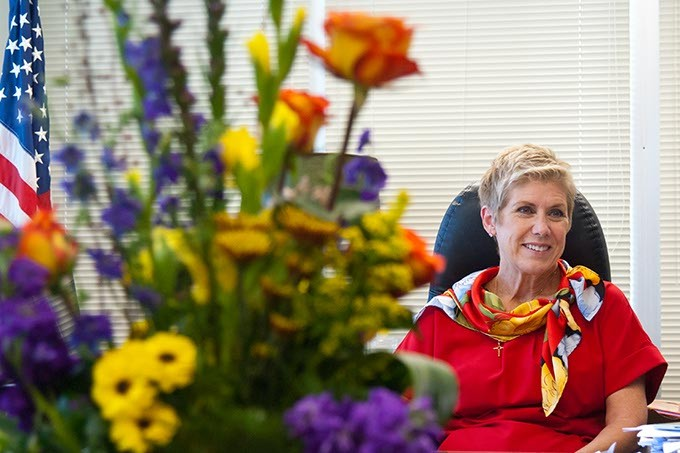 Janet Barresi, the outgoing State Superintendent of Public Instruction, discusses her term beyond a large, colorful arrangement of flowers, in her state office recently.  mh