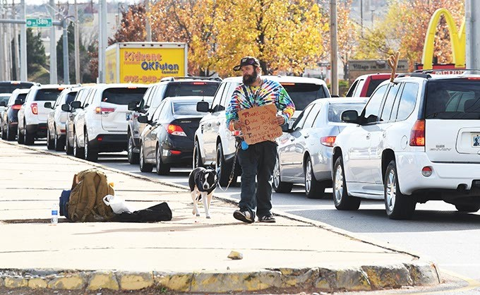 A man and his dog panhandles from the median at NW 140th and Pennsylvania Avenue in Oklahoma City, 12-8-15. - MARK HANCOCK