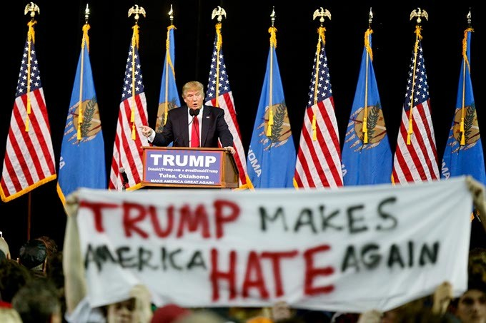 Republican Presidential candidate Donald Trump addresses a crowd while protestors hold up a sign during his rally at the Mabee Center at Oral Roberts University in Tulsa, Jan. 20, 2016. (Photo Ian Maule / Tulsa World / File / Provided)