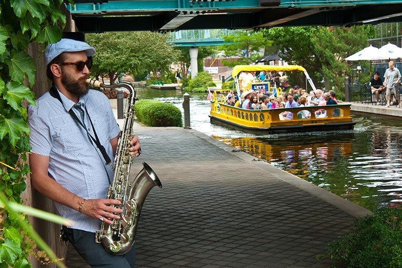 "Out of the Box performer, David Bruster, plays along the Bricktown Canal as a Water Taxi, ""captive audience"" cruises his way, 7-19-14.  mh  mh"