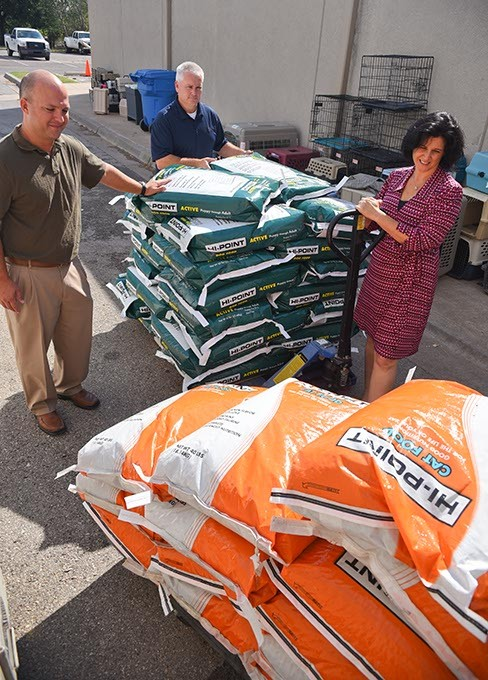 Julie Bank, animal welfare superintendent with the Oklahoma City Animal Shelter, receives donation of dog and cat food from Shawnee Milling Company's, left to right, Joe Ford, vice president of operations, and Brent Thompson, feed sales director 9-24-15.  (Mark Hancock