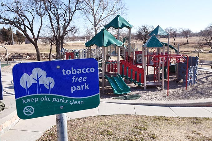 """Existing """"Tobacco Free Park"""" sign at a playground area of Will Rogers Park, off North Portland Avenue in Oklahoma City, 12-23-15. - MARK HANCOCK"""