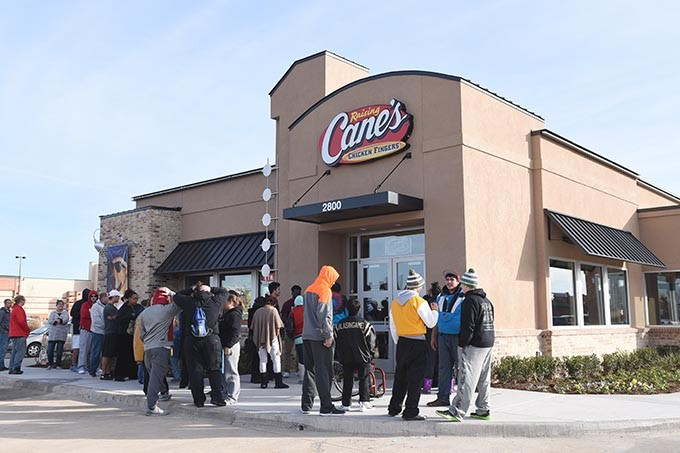 People waiting outside of the new, 250th Raising Canes restaurant in Midwest City for its Grand Opening, 12-10-15.  The first 20 customers get free Canes once a week for a year. - MARK HANCOCK