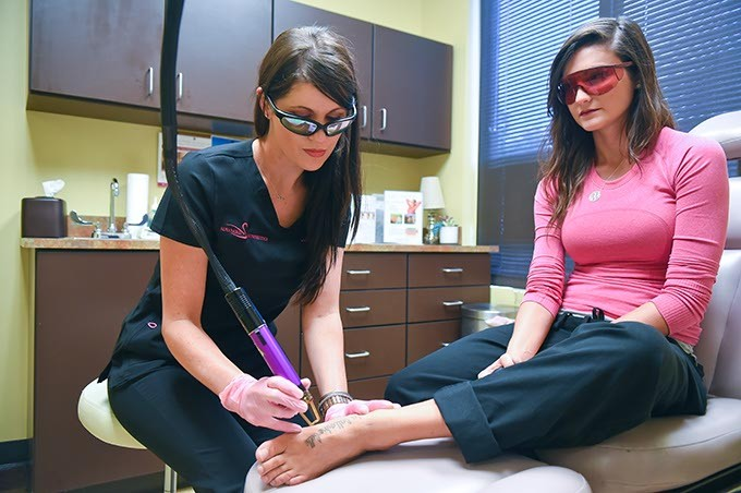 Lyric Mallow, an RN at Advanced Aesthetics, demonstrates how she uses a laser for the tattoo removal process with a fellow RN Amber Watson. (Mark Hancock)