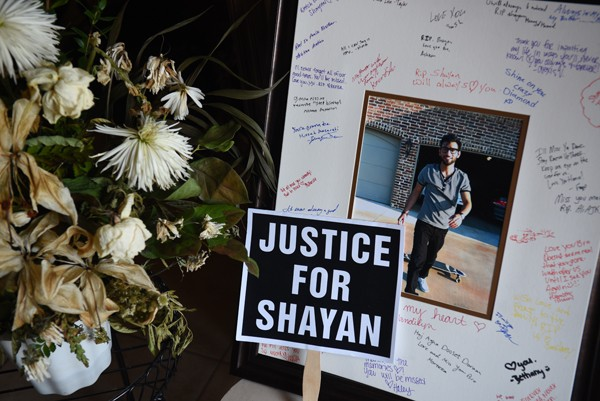 An informal portrait of Shayan Mazroe just getting off his scateboard taken by Mandi Leegard, with signatures and messages from friends, a proped-up yard sign for justice, and a vase of wilted flowers, create a small memorial inside Mandi Leegard's Edmond Home, 10-7-15. - MARK HANCOCK