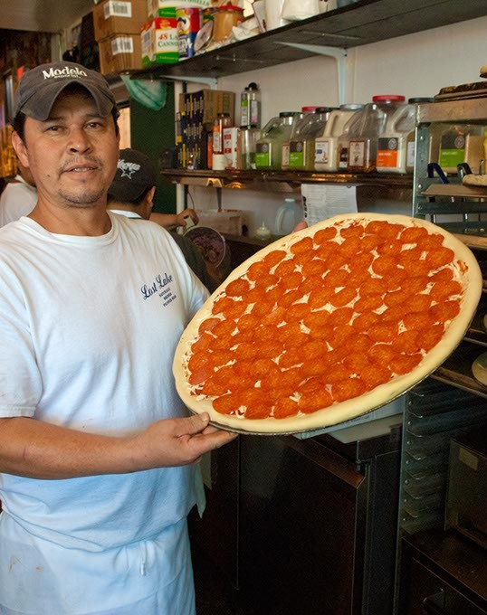 Jorge Resendiz with a large pepperoni pizza in the oven for baking, at Empire Slice House.  mh