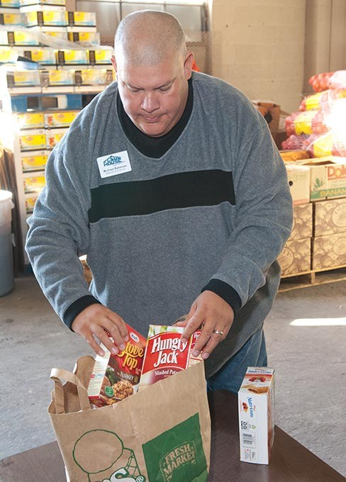 Mike Bateman, executive director at Jesus House, aranges items in a grocery sack, as an example of what will be given to low-income families during this years food basket hand out, in the donations warehouse at Jesus House.  mh