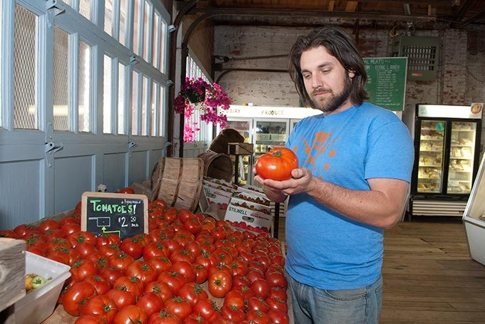 Matt Burch examines a tomato at the Urban Agrarian, in OKC's Farmers Market,  5-3-13 - MARK HANCOCK