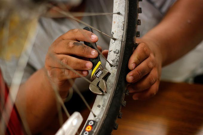 Ruben Cervantes works on a bicycle wheel at Emerson High School in Oklahoma City, Wednesday, May 6, 2015. - GARETT FISBECK