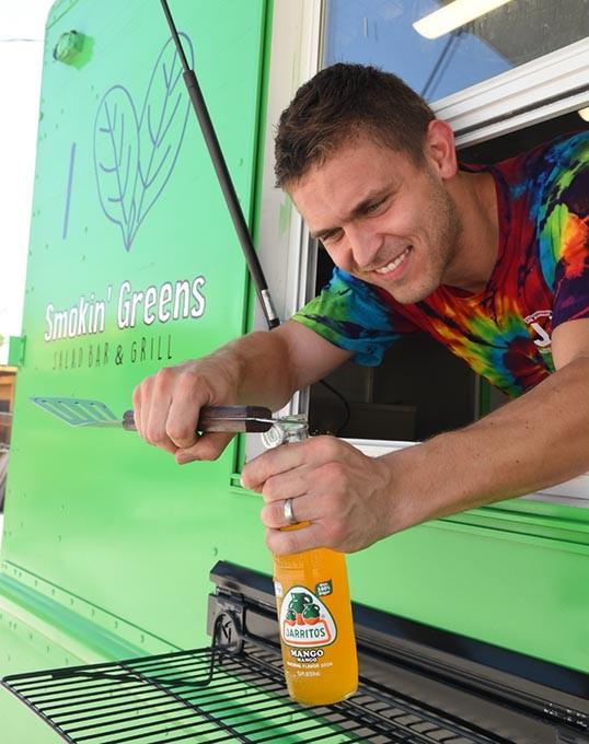 Levi Schmidt, owner of Smokin' Greens food truck, opens a Mango Jarritos for a customer, recently at Bleu Gartin.  mh