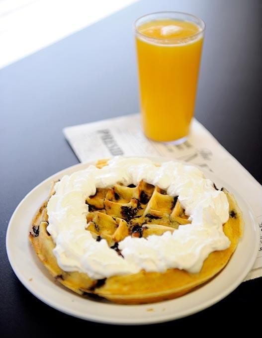 Blueberry waffle with whipped cream and orange juice at Around the Corner in Edmond, Wednesday, Feb. 11, 2015. - GARETT FISBECK