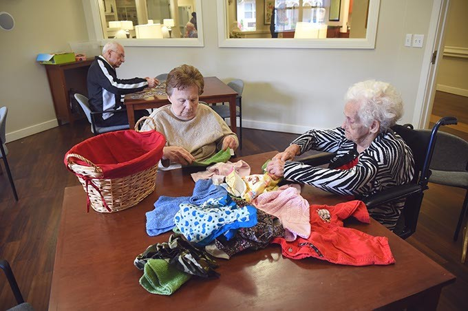 Residents at Prairie Winds Alzheimer's Special Care Center partake in daily rituals as part of Alzheimer's therapy such as folding clothes from laundry baskets and working puzzles.  mh