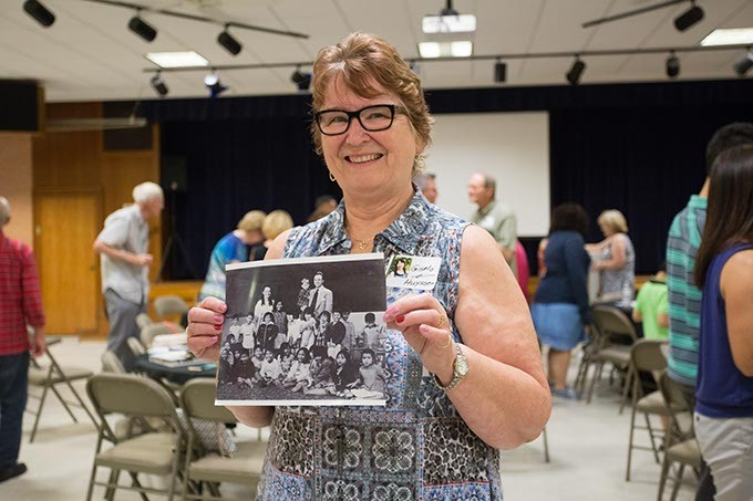 Gisela Huyssen holds a photo of the 23 children with her and her husband. Gisela Huyssen and her husband Ulrich Huyssen adopted 23 Vietnamese children to American families at the end of the Vietnam war on Saturday, July 2, 2016 in Oklahoma City. - EMMY VERDIN