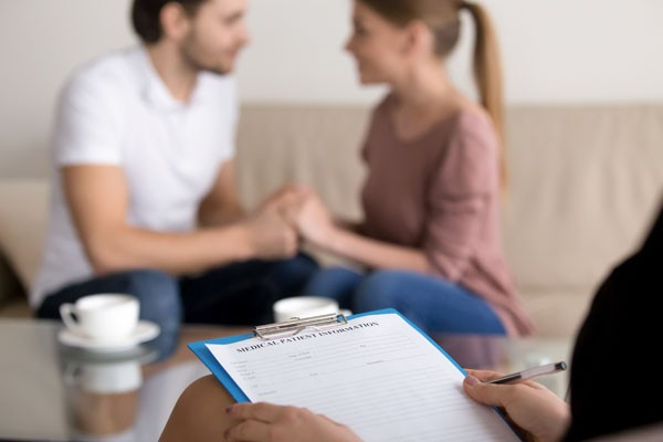 Successful therapy session with family couple in the background, reconciliation after argument, making peace, focus on hands of female psychologist holding clipboard with medical card, close up - BIGSTOCK