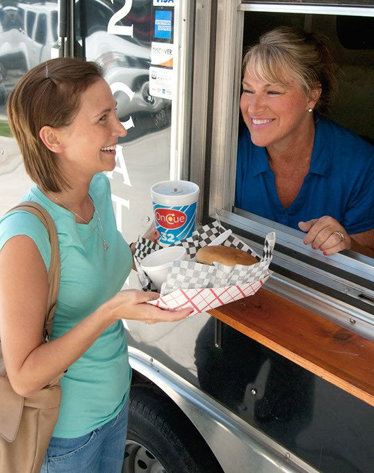 Melanie Wilson gets some lunch from Jan Clem at the window of Klemm's Smoke Haus, on location at Oklahoma Employee's Credid Union, 8-1-14.  mh