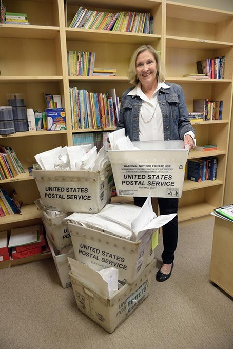 Cheri Fuller poses for a photo with boxes of letters and books to be sent to children of parents who are incarcerated at the Oklahoma Messages Project in Edmond, Wednesday, Dec. 7, 2016. - GARETT FISBECK
