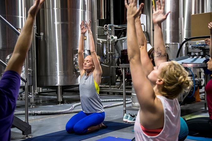 Surrounded by brewing equipment, Instructor Brooke Larson leads a class of Beer Yoga, at Coop Ale Works in southwest Oklahoma City, 10-15-2016. - MARK HANCOCK