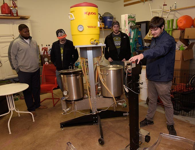 Evan Smith shows a test batch brewing kit at Vanessa House Beer Company as Nick White, Andrew Carrales, and Justin Wright look on, Monday, Nov. 21, 2016. - GARETT FISBECK