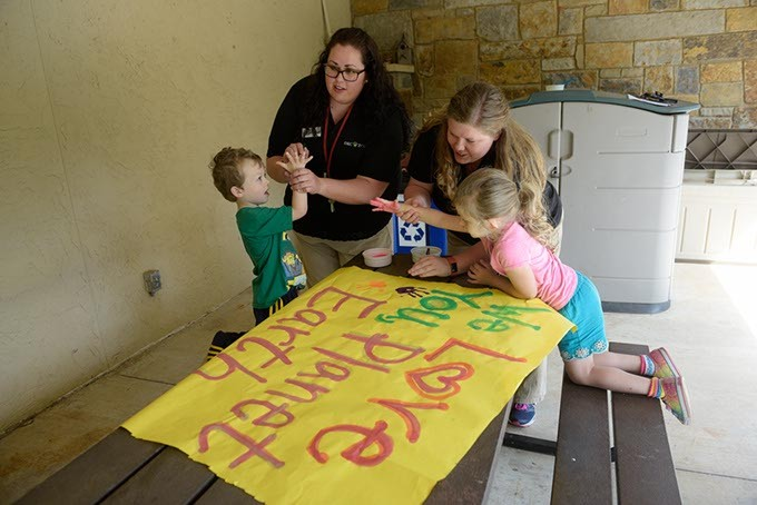 Lindsay Biggs and Rachael Robinson help children make an Earth Day banner at the Oklahoma City Zoo Wednesday, April 19, 2017. - GARETT FISBECK