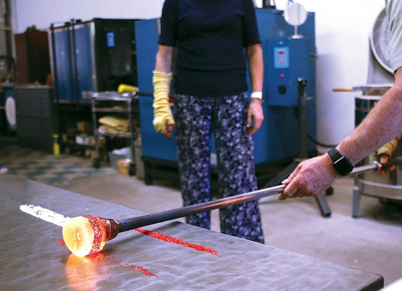Lee Kessinger rolls colored glass pieces onto hot glass at G Gallery & Glass Studio in Guthrie. (Cara Johnson)